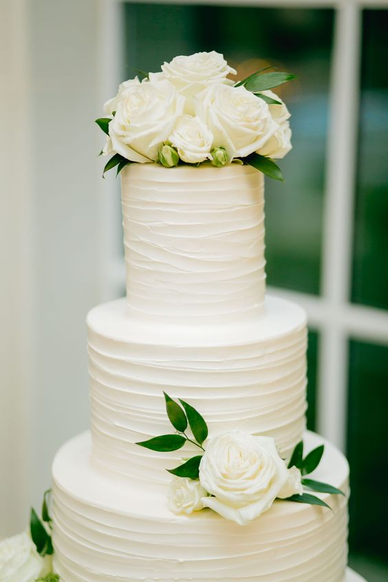 This stunning and modern all white wedding cake was made even more perfect for our bride and groom with real white garden roses and touches of greenery added around the edges. #weddingideas #roses #weddingcake